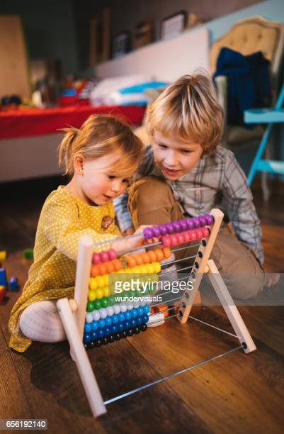 Boy and little girl playing with abacus on the floor