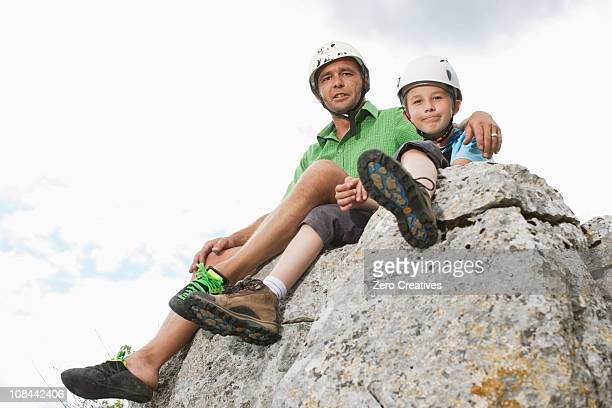 Boy and man sitting on a rock