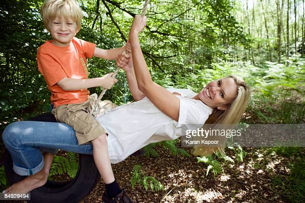 Boy and mom on tire swing