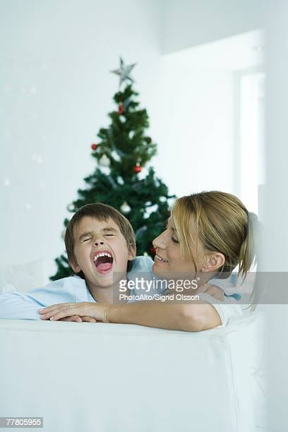 Boy and mother on sofa, boy screaming, Christmas tree in background