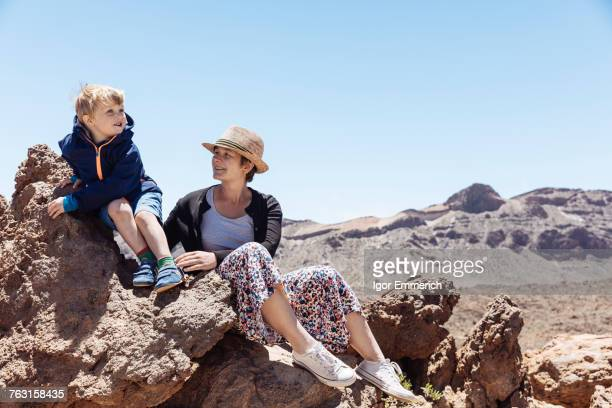 boy and mother sitting on rocks at mount teide, tenerife, canary islands - pico de teide stock pictures, royalty-free photos & images