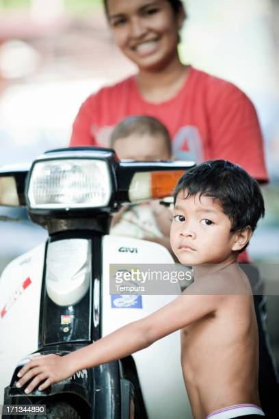 boy and mother standing next to motorcycle. - taman negara national park stock photos and pictures