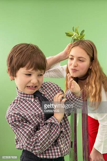 Boy and Pre-Teen Girl Holding Mistletoe