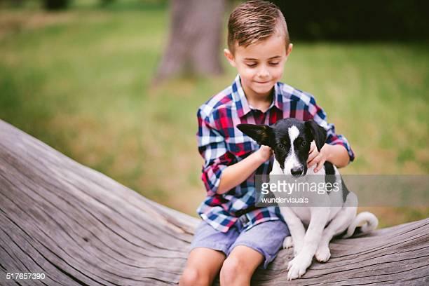 Junge und Welpe Hund sitzen auf Baum Zweig im Park