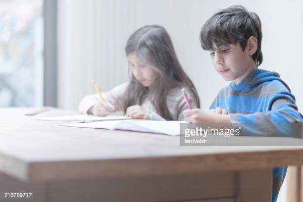 boy and sister doing homework at kitchen table - 10歳から11歳 ストックフォトと画像