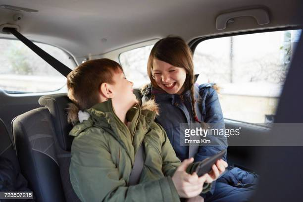 boy and sister laughing in car backseat - parka coat stock pictures, royalty-free photos & images