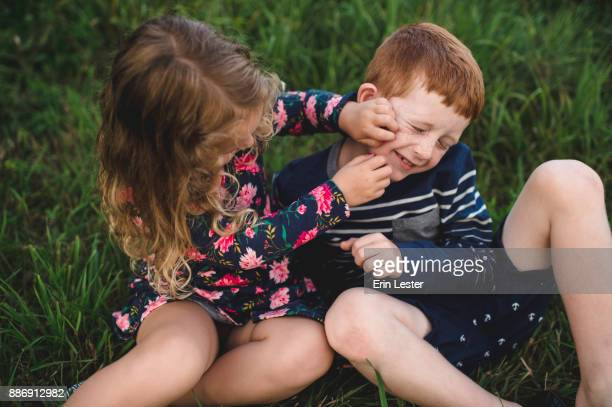 Boy and sister play fighting in field