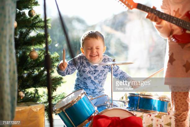 Boy and sister playing toy drum kit and guitar on christmas day