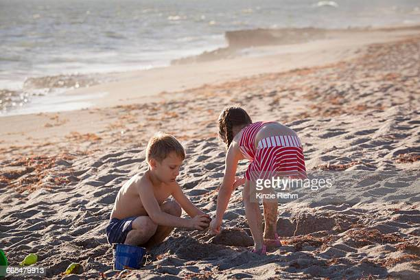 boy and sister playing with sand on beach, blowing rocks preserve, jupiter island, florida, usa - blowing rocks preserve stock photos and pictures