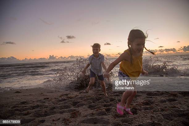 boy and sister running away from splashing waves at sunrise, blowing rocks preserve, jupiter island, florida, usa - blowing rocks preserve stock photos and pictures