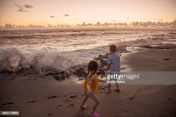 boy and sister running away from splashing waves on beach at sunrise, blowing rocks preserve, jupiter island, florida, usa - blowing rocks preserve stock photos and pictures