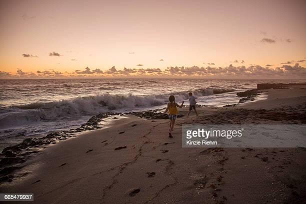 boy and sister running on beach at sunrise, blowing rocks preserve, jupiter island, florida, usa - blowing rocks preserve stock photos and pictures