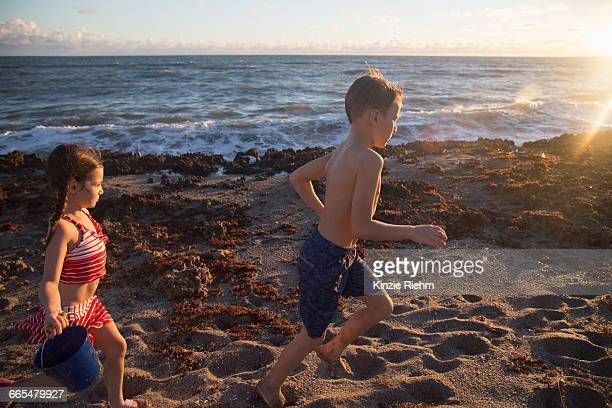 boy and sister running on beach, blowing rocks preserve, jupiter island, florida, usa - blowing rocks preserve stock photos and pictures