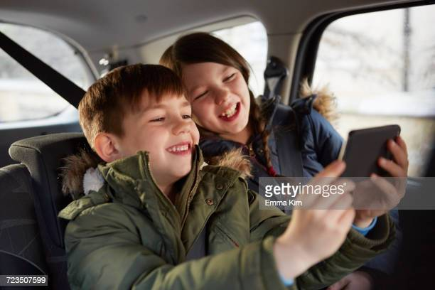 Boy and sister taking laughing selfie in car backseat