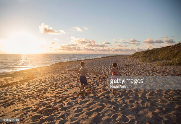 boy and sister walking along beach at sunrise, blowing rocks preserve, jupiter island, florida, usa - blowing rocks preserve stock photos and pictures