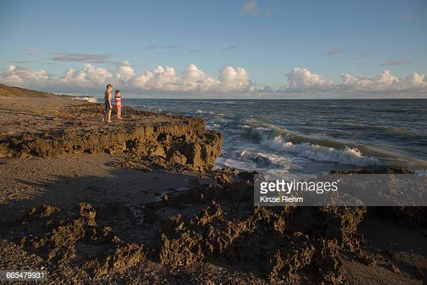 Boy and sister watching ocean waves, Blowing Rocks Preserve, Jupiter Island, Florida, USA