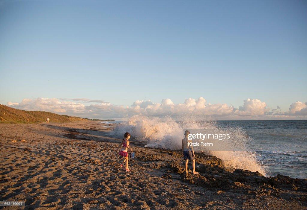 Boy and sister watching splashing waves from beach, Blowing Rocks Preserve, Jupiter Island, Florida, USA : Stock Photo