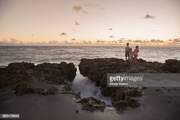 boy and sisters looking out from rocks at sunrise, blowing rocks preserve, jupiter island, florida, usa - blowing rocks preserve stock photos and pictures