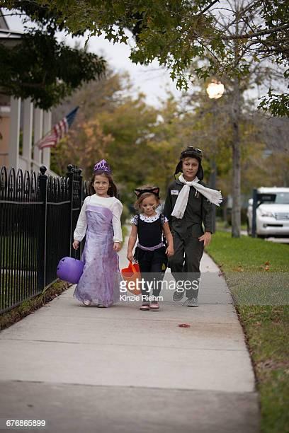 Boy and sisters walking along sidewalk trick or treating
