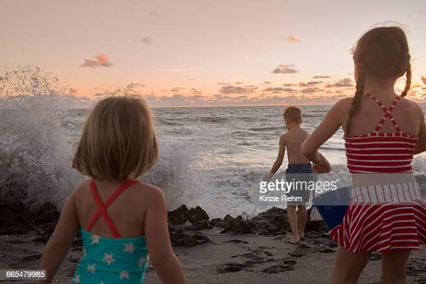 boy and sisters watching splashing waves at sunrise, blowing rocks preserve, jupiter island, florida, usa - blowing rocks preserve stock photos and pictures