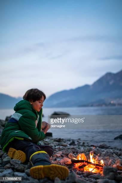 少年と小さな焚き火の近く湖の岸 - イタリア コモ県 ストックフォトと画像