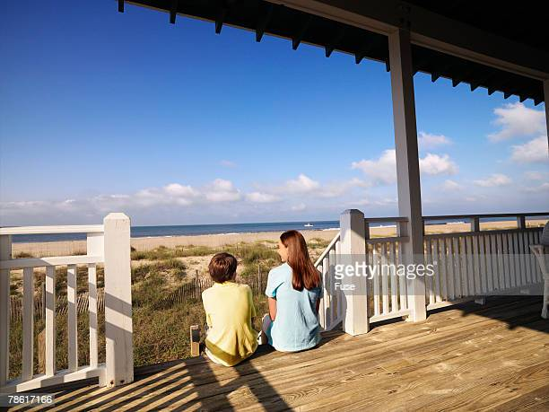 Boy and Teenage Girl Sitting on Porch of Beach House