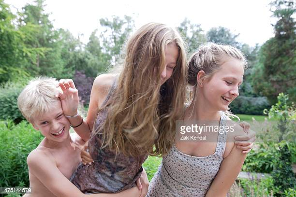 boy and teenage girls play fighting in garden - female wrestling holds stockfoto's en -beelden