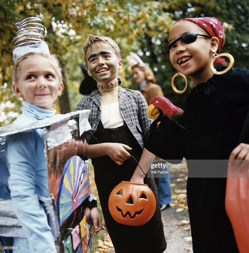 Boy And Two Girls In Halloween Costumes Do Trick Or Treat Photo