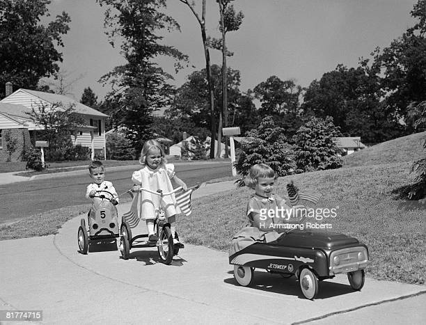 Boy and two girls on suburban sidewalk, riding tricycle and toy cars.