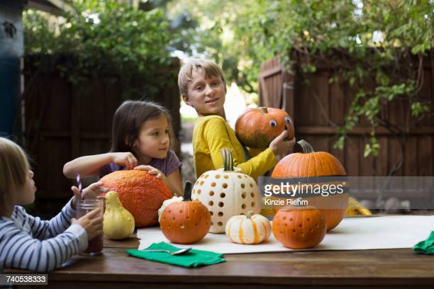 Boy and two sisters preparing pumpkins on garden table