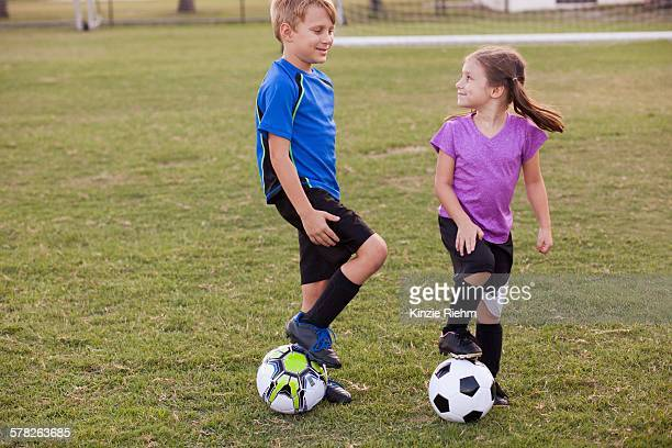 Boy and younger sister with footballs on practice pitch