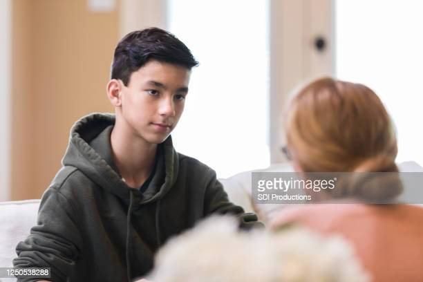 boy angry at being caught; mother appeals - boys stock pictures, royalty-free photos & images