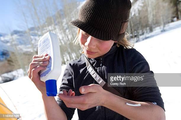 A boy applies sunscreen before snowboarding in the California backcountry.