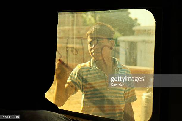 CONTENT] A boy approaches a stationary train window at a station and starts to write in the dust with his finger Jaisalmer Rajasthan India