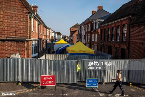 A boy approaches as a police officer stands at a cordon with forensics tents by a supported housing project in Salisbury after a major incident was...