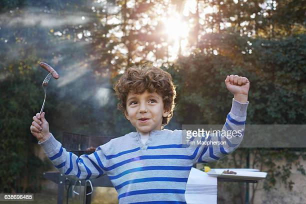 boy arms raised holding sausage on fork smiling - snag tree stock pictures, royalty-free photos & images
