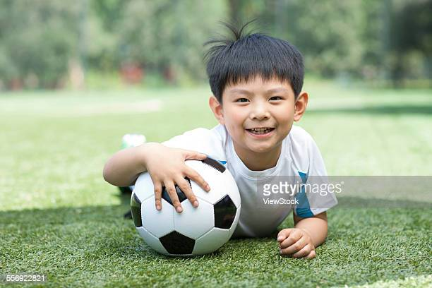 A boy around football playing on the grass