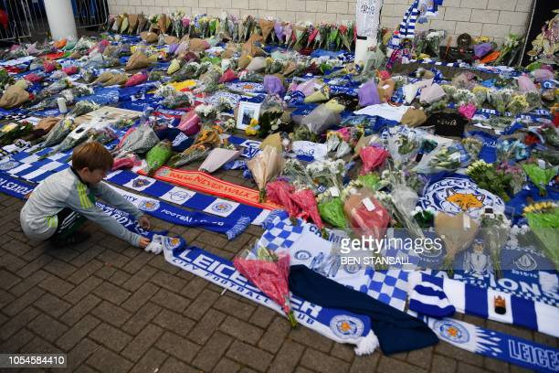 A boy arranges a club scarf around floral tributes piled outside Leicester City Football Club's King Power Stadium in Leicester eastern England on...