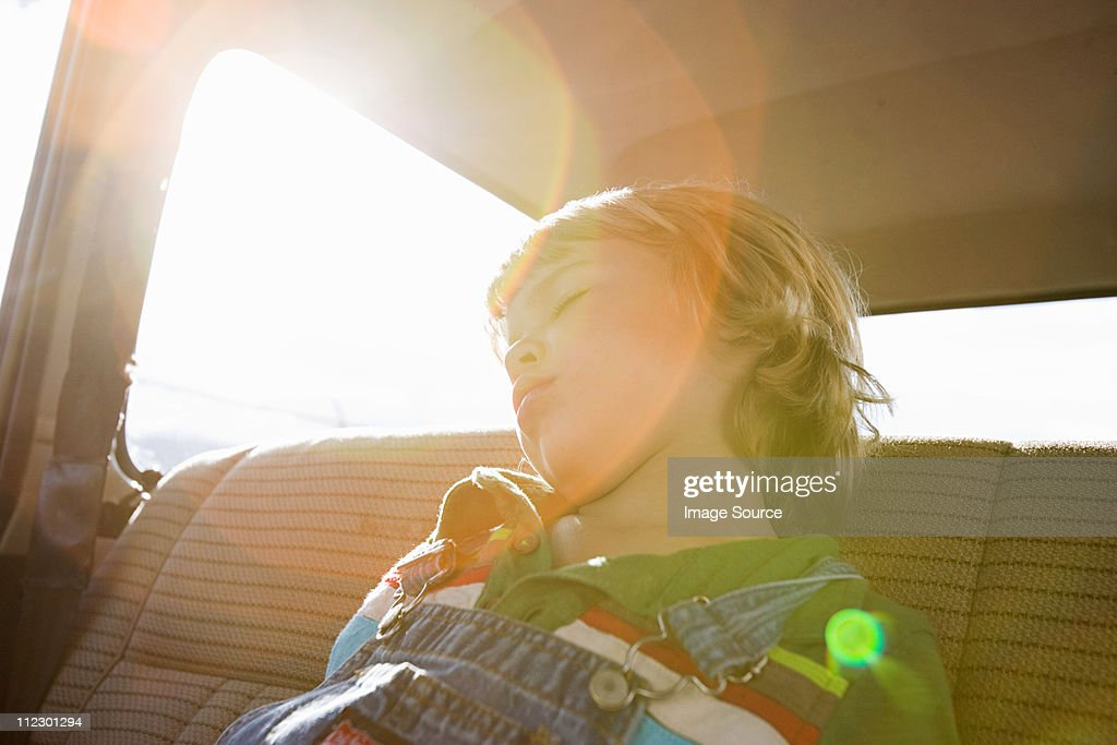 Boy asleep in back seat of car : Stock Photo