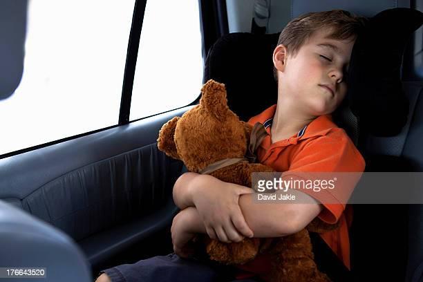 Boy asleep in child safety seat in car holding teddy bear