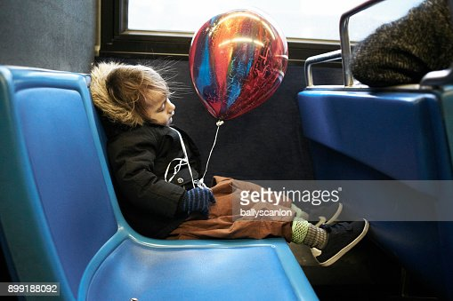 Boy Asleep On Bus With Balloon