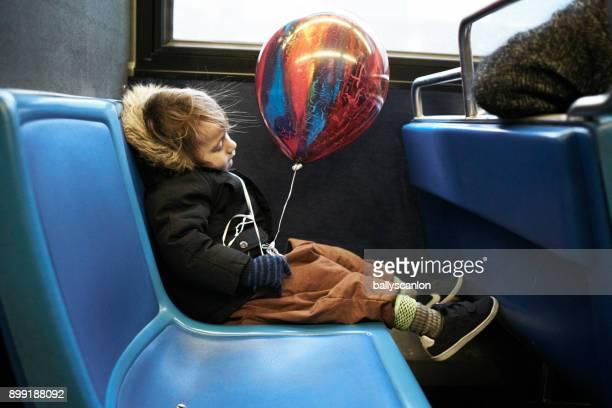 Boy Asleep On Bus With Balloon
