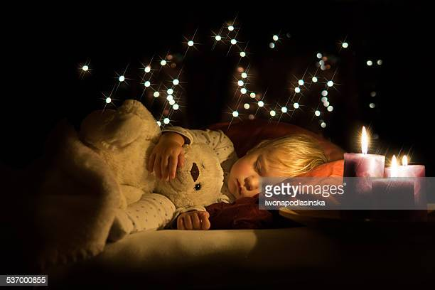 Boy asleep with teddy and warm candle light