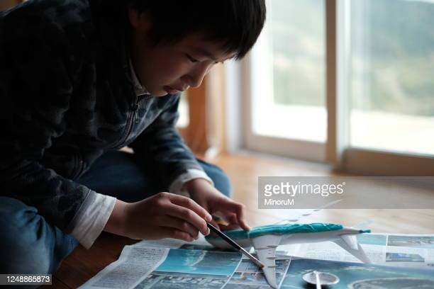 boy assembling a plastic model of airplane - model kit stock pictures, royalty-free photos & images