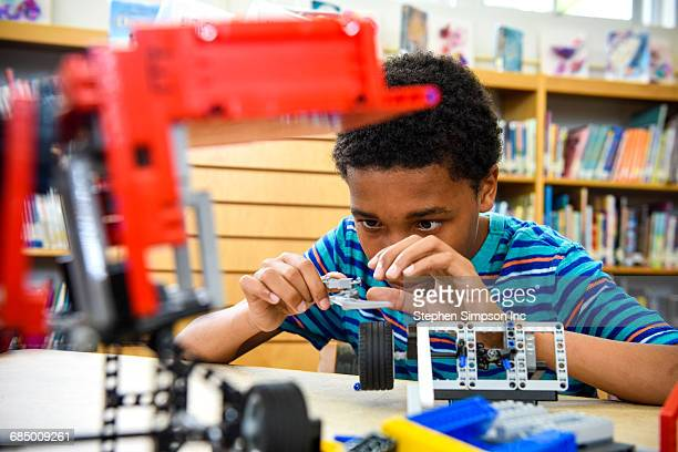 boy assembling plastic blocks in library - science photo library stock pictures, royalty-free photos & images