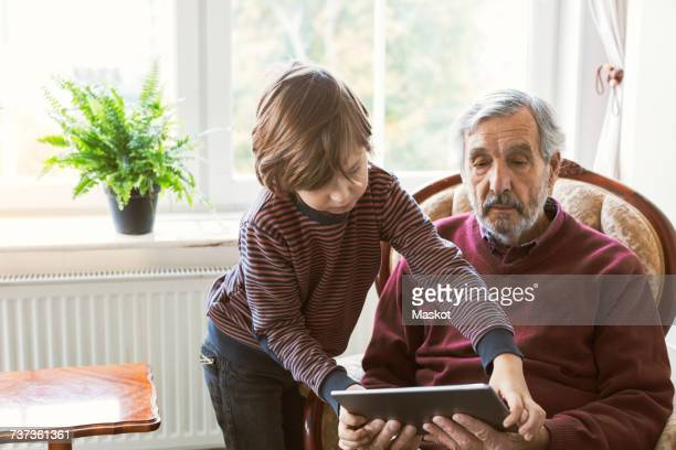Boy assisting great grandfather in using digital tablet at home