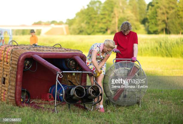 Boy Assisting Pilot In Preparing Hot Air Balloon On Grassy Field During Sunset