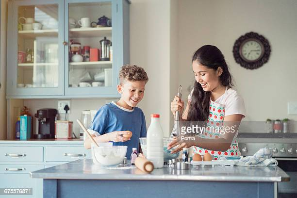 boy assisting sister in baking cake at home - sister stock pictures, royalty-free photos & images