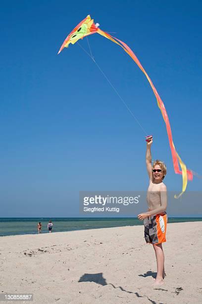 Boy at a beach flying a kite, Poel Island, Mecklenburg-Western Pomerania, Germany, Europe