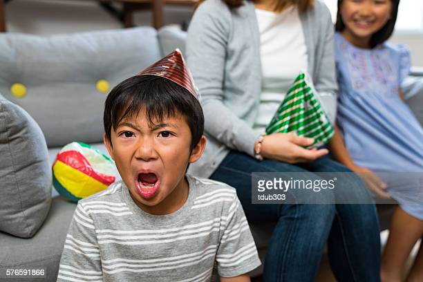 Boy at a party looking very angry and upset